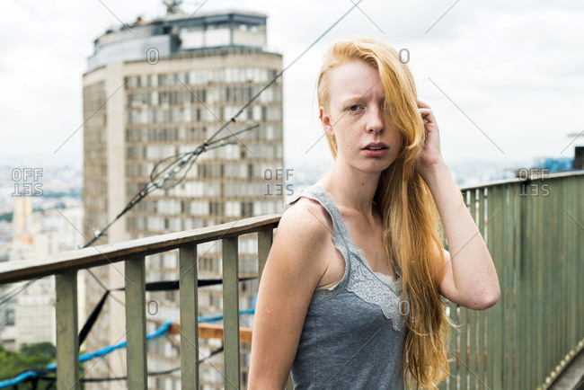 Woman with freckles on urban rooftop