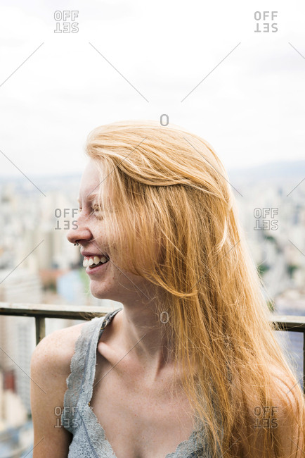 Smiling woman with freckles over city