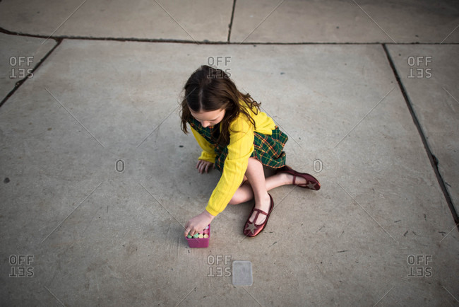 Girl in plaid drawing with chalk