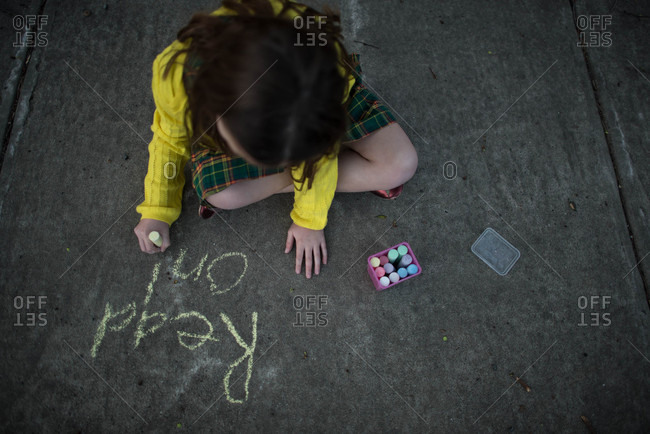 Girl writing words with chalk