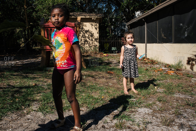Two little girls playing in a backyard