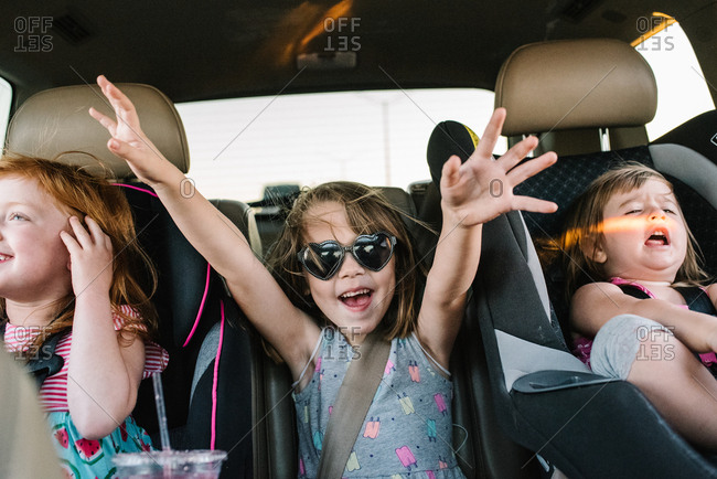 Little girls riding in back seat of car