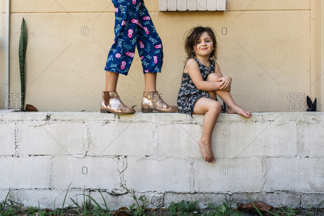 Two little girls hanging out on a cinder block wall