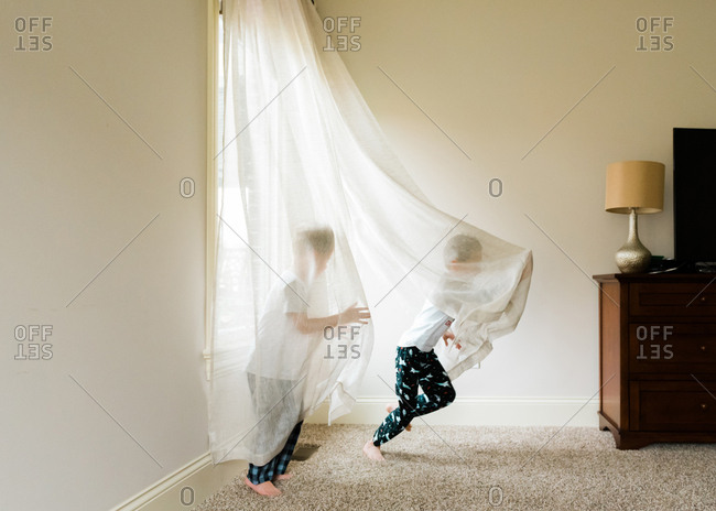 Brothers goofing around in sheer curtains