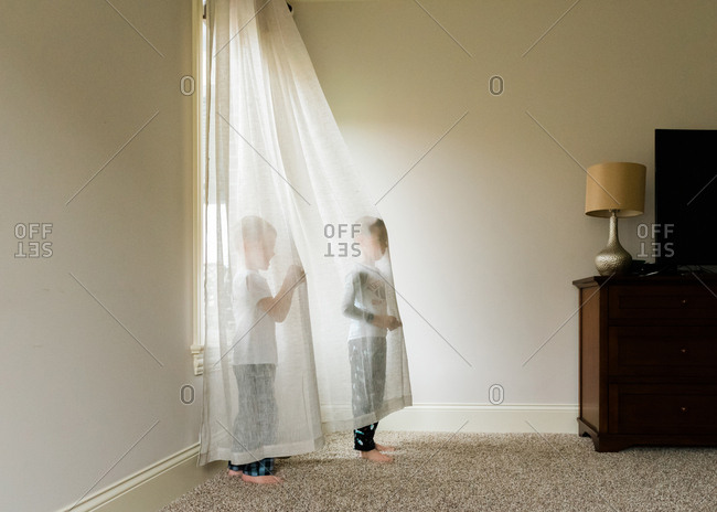 Little boys goofing around in sheer curtains