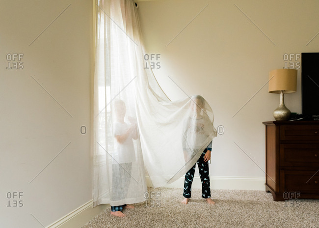 Two brothers goofing around in sheer curtains
