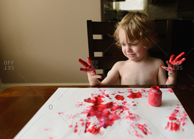 Little boy painting with red finger paint