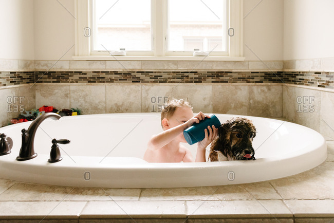 Boy bathing with dog