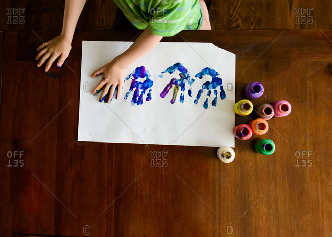 Overhead view of boy making handprint paint picture