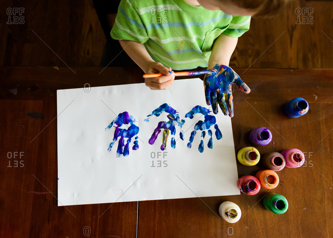 Young boy making handprint paint picture