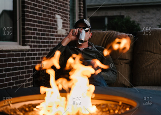 Man sitting by fire pit drinking a beer