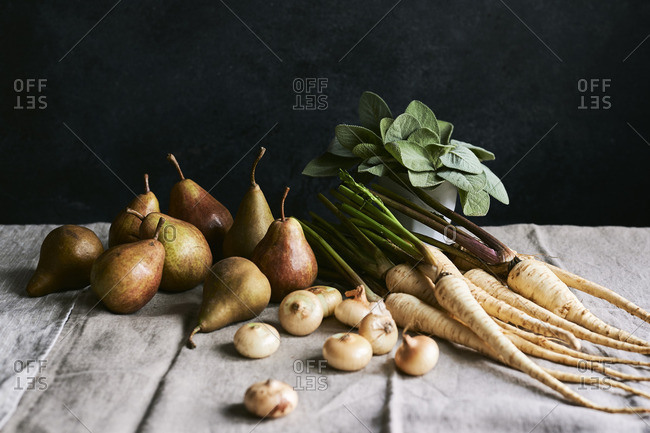 Still life of fresh ingredients; parsnips, pears, onions and sage