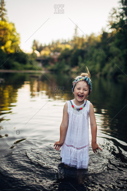 Young girl laughing while standing in a river