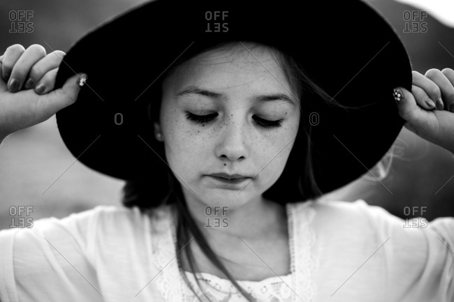 Black and white portrait of a young girl with her hands on her hat