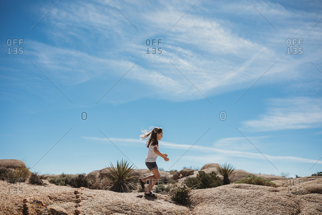Young girl climbing on rocks at Joshua Tree National Park