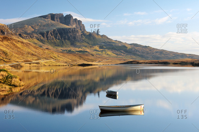 The Storr and two boats reflecting on Loch Fada in the morning light. Isle of Skye, Scotland.