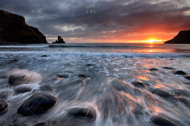 Sunset at the rocky shore of Talisker bay on the Isle of Skye, Scotland.