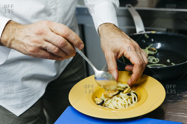 Chef plating a pasta dish with shellfish
