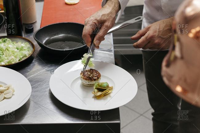 Chef adding lettuce to a sandwich
