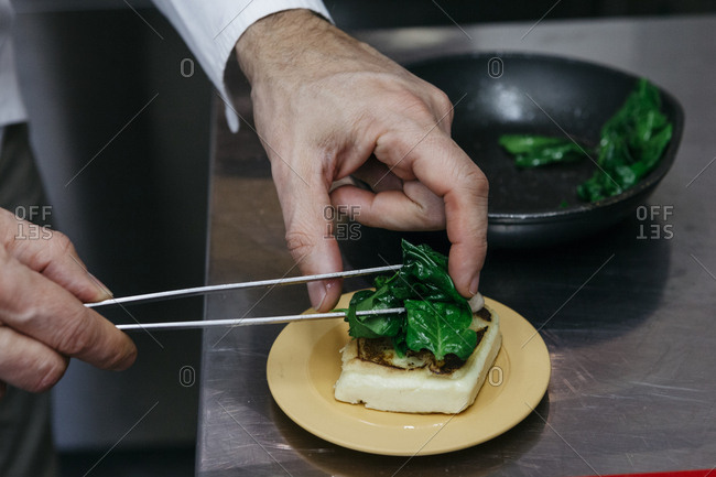 Chef preparing an appetizer topped with wilted spinach