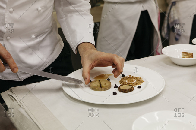 Chef preparing a dessert on plate