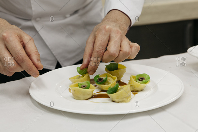 Chef preparing a plate of homemade tortellini