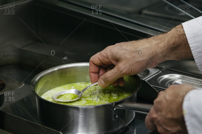 Chef preparing green sauce in pan on stove