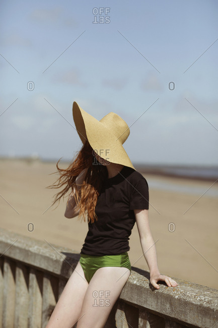 Young woman in a sun hat leaning against a railing at a beach