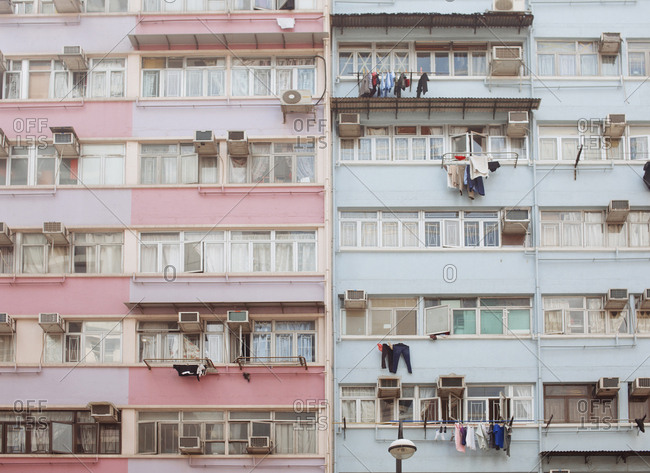 Clothing hanging from balconies of tall colorful buildings