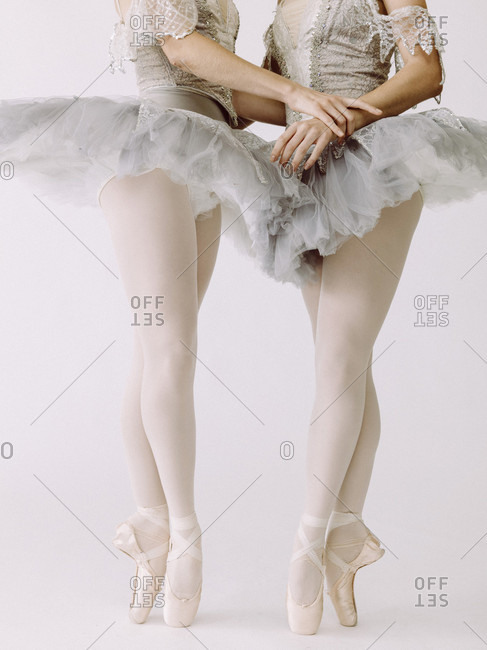 Two ballet dancers standing next to each other and holding hands