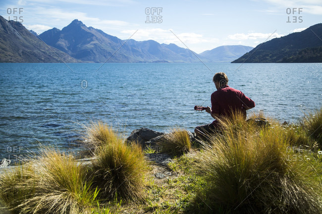 Man Playing The Guitar Along The Side Of Lake Wakatipu In New Zealand