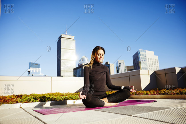 A Woman Practicing Yoga On A Rooftop Deck