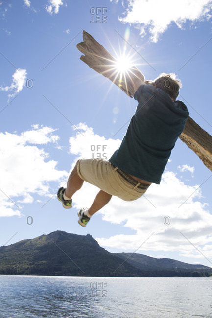 Mature man hangs from driftwood above lake and mountains