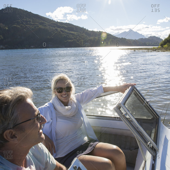 Portrait of mature couple in motorboat on mountain lake