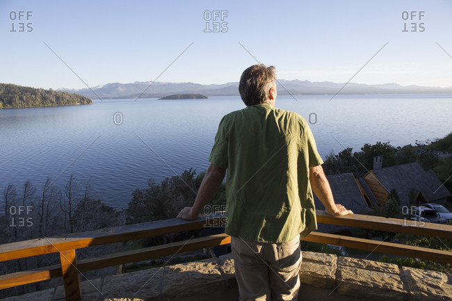 Mature man looks over lakes and mountains from balcony