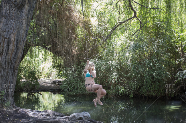 Mature woman swings from tree on rope into freshwater lagoon