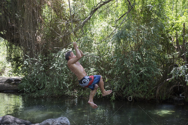 Mature man swings from tree on rope into freshwater lagoon