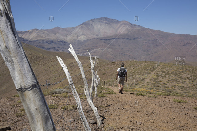 View past wooden fence posts to hiker on desert trail in mountains