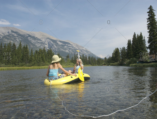 Two young girls float down creek in mountains