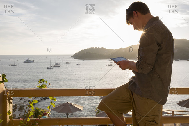 Young man relaxes on hotel veranda, uses digital tablet