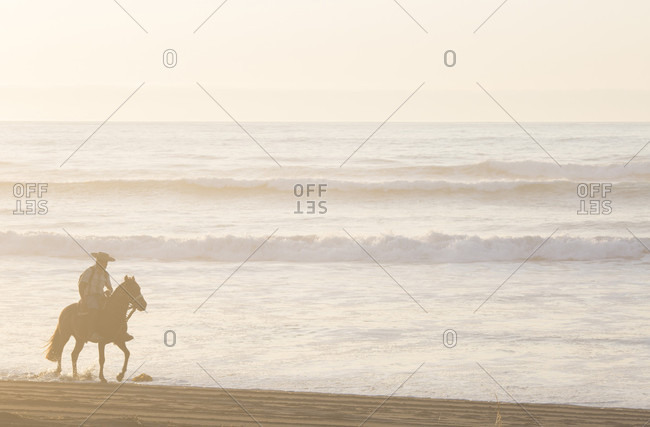 Gaucho/cowboy rides along Pacific surf edge
