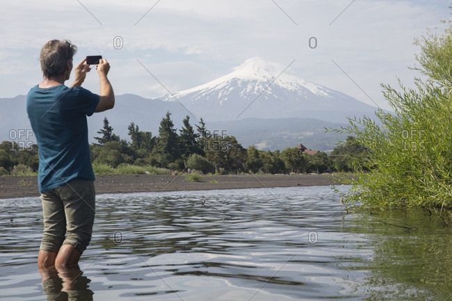 Man takes smart phone pic across lake, Villarrica volcano