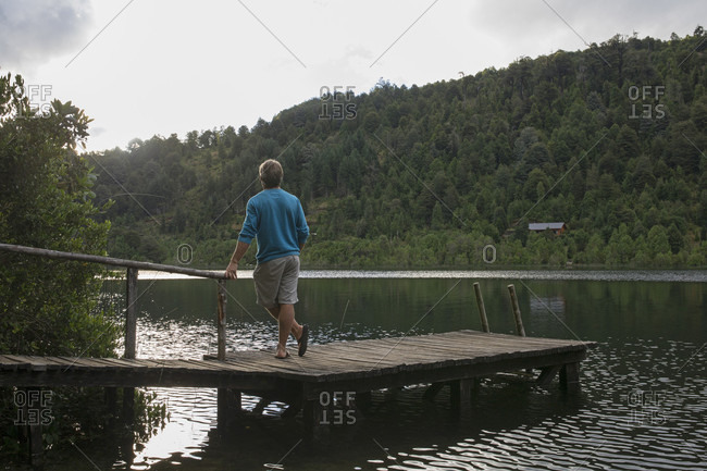 Man looks across lake from wooden pier