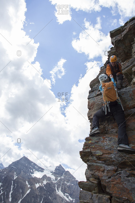 Mountain guide assists woman climber up rock face above mountains