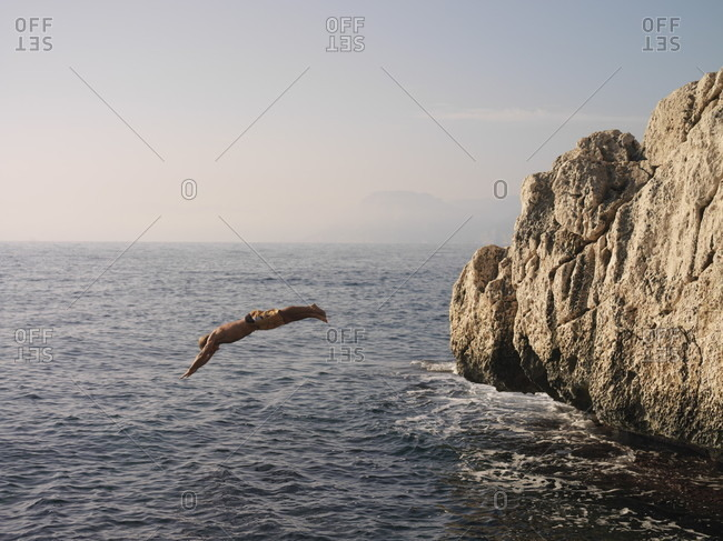 Man dives into sea from rock bluff at sunset