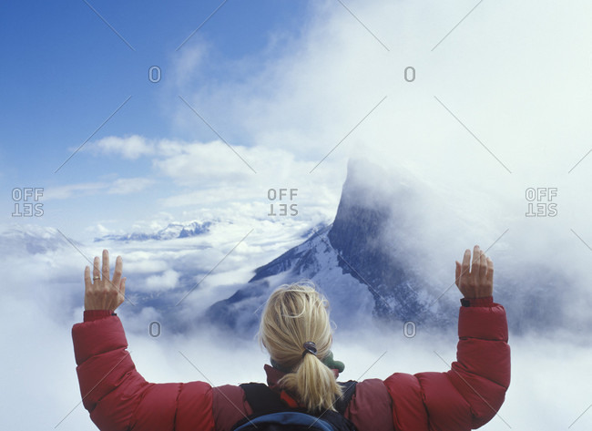 Head and shoulders of woman in clouds above mountains