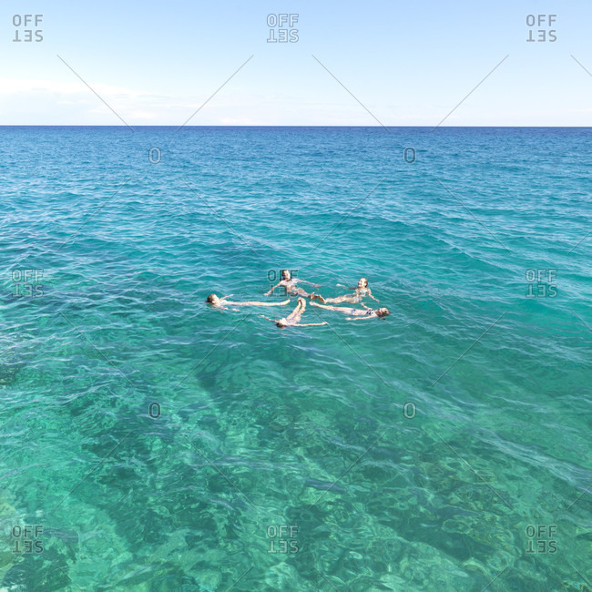 Five teenage girls make star shape with bodies while floating in sea