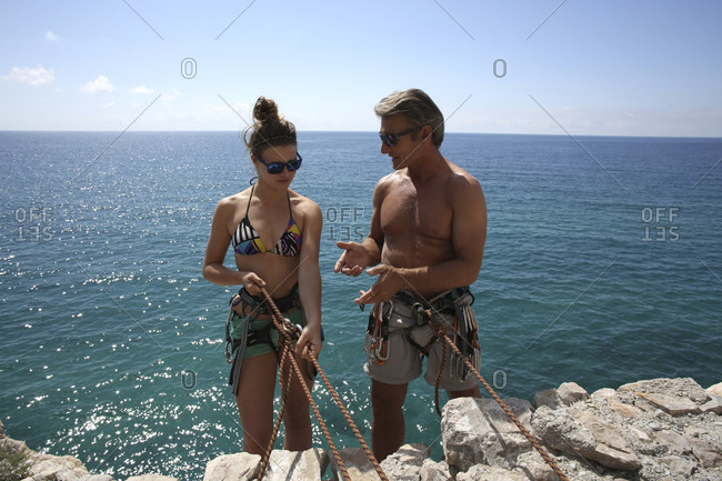 Teen girl gets in climbing instruction from father above sea