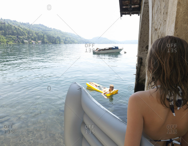 POV past tween girl with floating mattress to lake