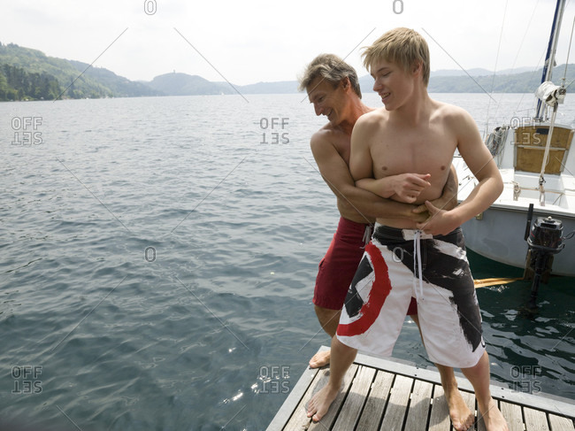 Father wrestles with young adult son on dock